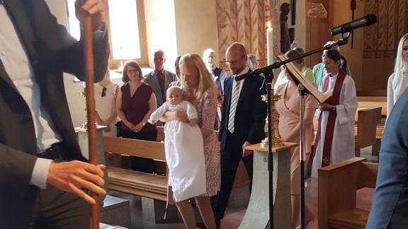 En mamma med en bebis iförd dopklänning i famnen som tågar framåt i mittgången följd av pappan, några faddrar och en präst. De lyssna på dopsånger.