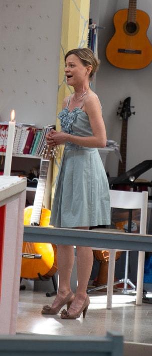 Helkroppsbild från sidan på Petra Valman när hon sjunger på en vigsel i en kyrka.